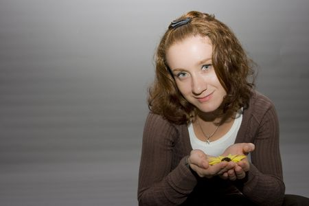 portrait of a beautiful redhaired girl holding a yellow flower in her hands