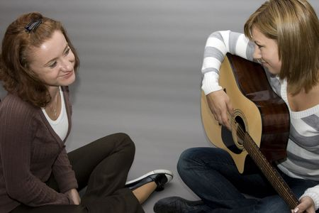 two girls. one girl playing guitar and the other one listening Stock Photo