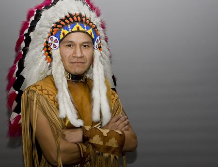 hat with feather: Portrait of a native american in a studio
