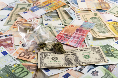 swiss franc note: Medicinal marijuana on a background of lots of bills of mixed currency and value of euro, dollars and swiss francs