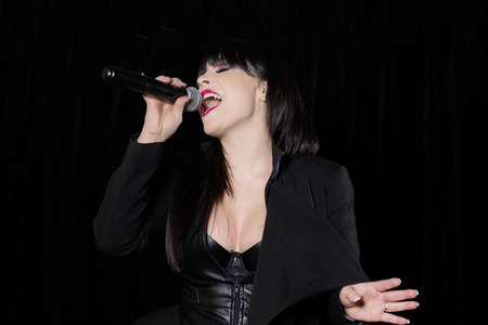 Beautiful singer singing with a microphone on stage Stock Photo