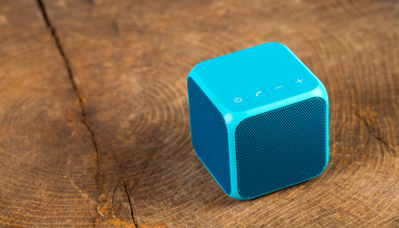 Blue bluetooth speaker cube on wood background Stock Photo