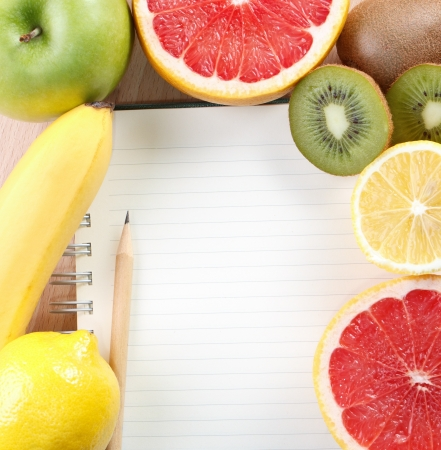 Directly above close-up view of a table with a notebook and tropical fruit photo