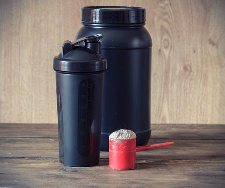 Wei-eiwit poeder in scoop en plastic shaker op houten achtergrond
