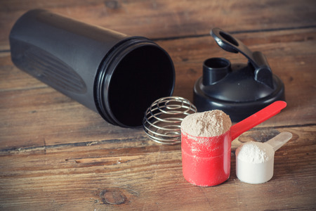 plastic scoop: Whey protein powder in scoop  and plastic shaker on wooden background