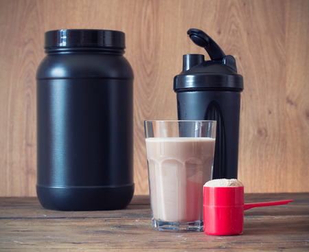 Whey protein powder in scoop  and plastic shaker on wooden background