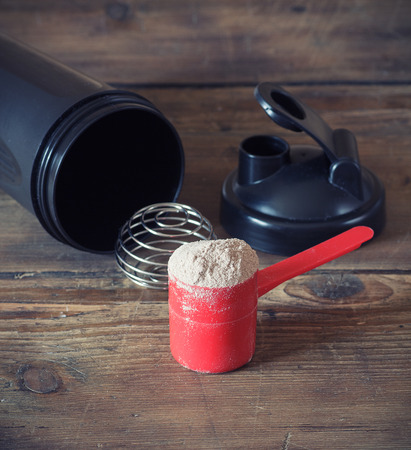 Whey protein powder in scoop and plastic shaker on wooden background Standard-Bild