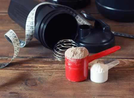 plastic scoop: Whey protein powder in scoop with vitamins and plastic shaker on wooden background