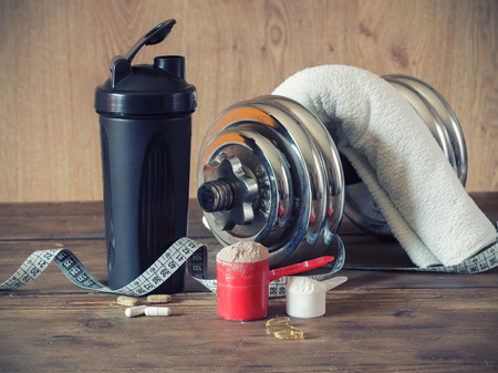 protein: Whey protein powder in scoop with vitamins and plastic shaker on wooden background