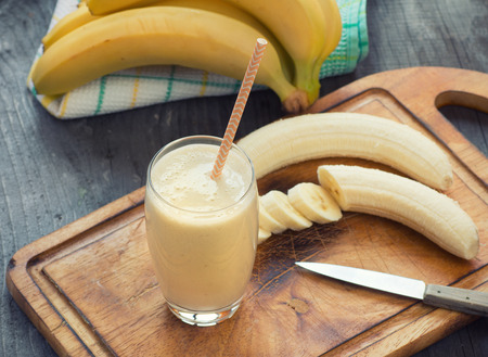 yellow to drink: Fresh made Banana smoothie on wooden background