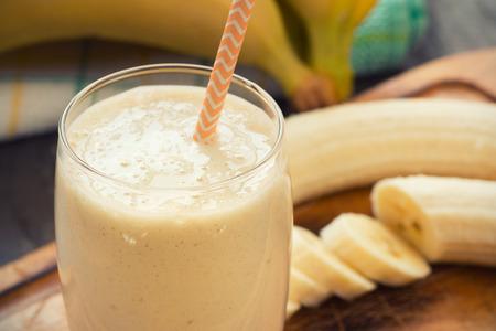 yogur: Batido de plátano hecho fresco en el fondo de madera Foto de archivo