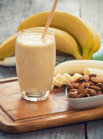 木製の背景にバナナのスムージーをたてください。 写真素材