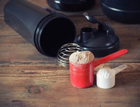 Whey protein powder in scoop with  plastic shaker on wooden background Stock Photo