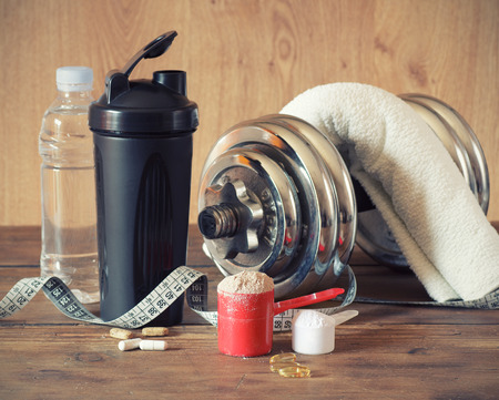 whey: Whey protein powder in scoop with vitamins and plastic shaker on wooden background