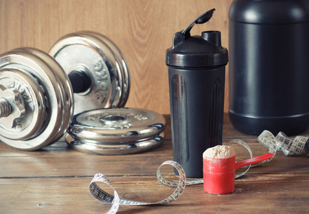 Whey protein powder in scoop with  plastic shaker on wooden background Imagens