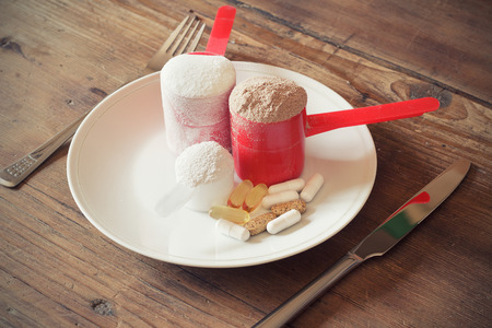 木製の背景上の板にビタミンとスクープにホエー蛋白質粉体