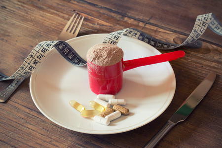 replacement: Whey protein powder in scoop with vitamins on plate on wooden background
