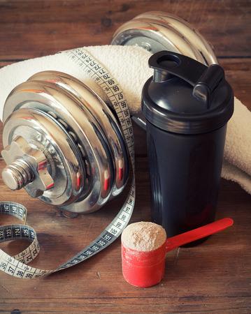salud y deporte: Polvo de prote�na de suero de leche en exclusiva con agitador de pl�stico sobre fondo de madera Foto de archivo