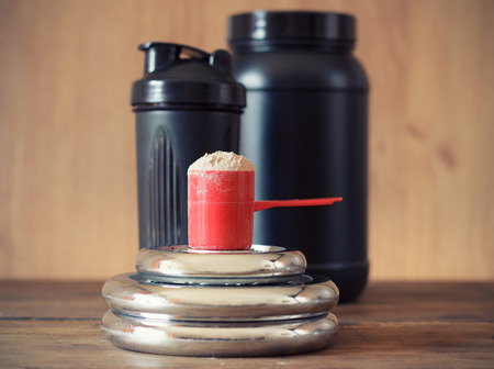 Whey Protein-Pulver in Schaufel mit Kunststoff Schüttler auf Holzuntergrund