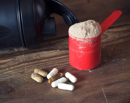 Whey protein powder in scoop with vitamins and plastic shaker on wooden background. Selective focus, shallow DOF Stok Fotoğraf - 39579270