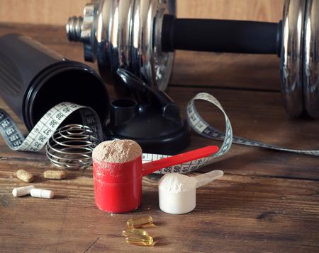 Wei-eiwit poeder in primeur met vitaminen en plastic shaker op houten achtergrond. Selectieve aandacht, ondiepe DOF
