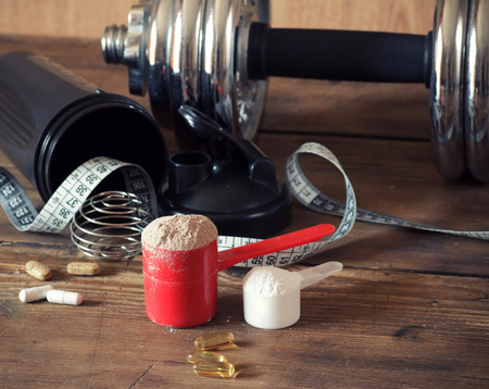Whey protein powder in scoop with vitamins and plastic shaker on wooden background. Selective focus, shallow DOF Stok Fotoğraf - 39579355