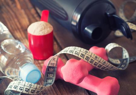 ホエー粉末状のテープ メジャー、ピンク ダンベル ブラック シェーカーと重量損失の概念