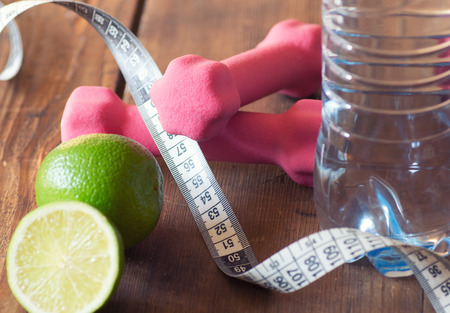 dumbell: weight loss concept with tape measure organic lime, pink dumbbells and natural bottle of water