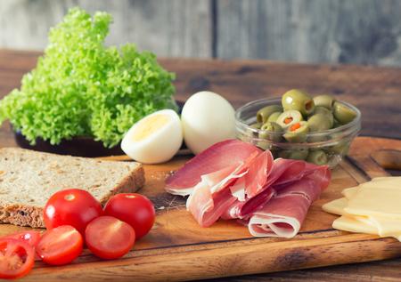 wholegrain mustard: preparing a sandwich with prosciutto in the kitchen