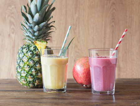 Pineapple and pomegranate smoothies on wooden table Stok Fotoğraf