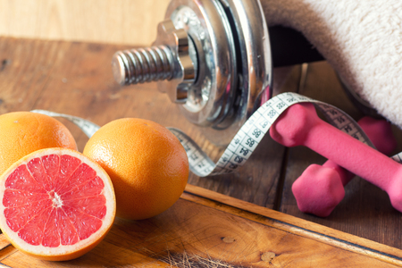 weight loss concept with tape measure organic grapefruit and dumbbells