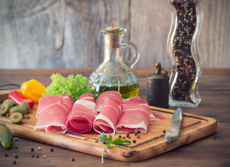 sliced prosciutto on a wooden board