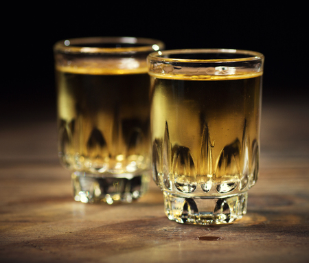Whisky in two glasses on a dark wooden background