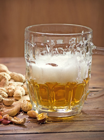 Beer and peanuts on the wooden background Stok Fotoğraf