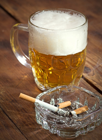Burning cigarette in a glass ashtray and mug of beer Stok Fotoğraf