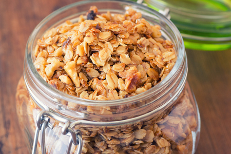 Fresh granola, muesli in a glass jar. copy space.Organic oat,almond and sunflower seeds