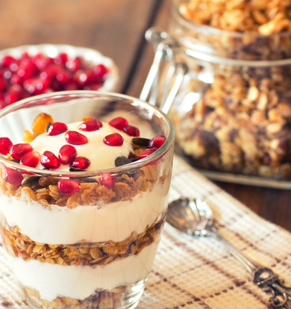 yogurt with homemade granola and pomegranate on the bright wooden board