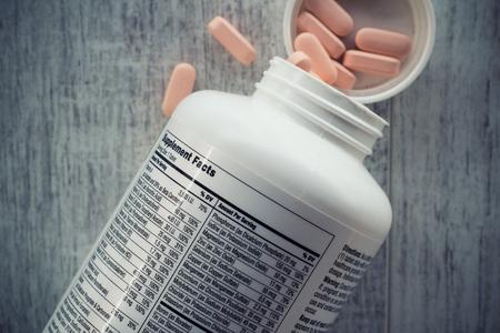 Hechos complementarios, detalle de una botella de vitaminas Foto de archivo