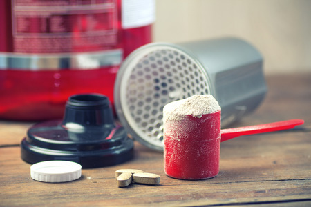 Fitness and sports concept with a scoop of protein powder necessary nutrition for muscle recovery after an intensive workout, next to a protein shaker Stockfoto
