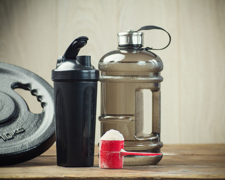 Fitness and sports concept with a  scoop of protein powder necessary nutrition for muscle recovery after an intensive workout, next to a protein shaker Stok Fotoğraf