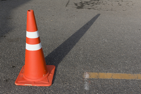 traffic cone, with white and orange stripes on gray asphalt. Imagens