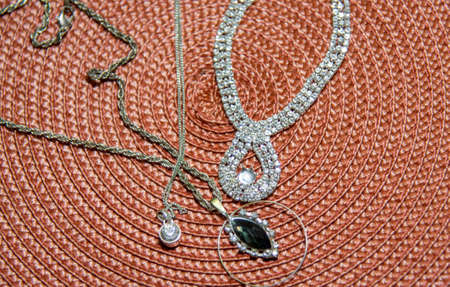 Jewelry pieces such as necklaces, earrings and cords arranged on a colored background. Art and style. Femininity. Jewels and bijouterie. fashion and sensuality. beauty.