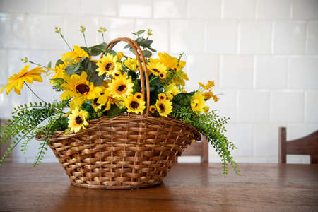A Craft Flower Arrangement in which a wicker basket with yellow sunflower flowers appears. Floriculture ornament to brighten up indoor environments. Inner decoration.