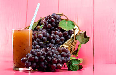 Glass of juice. Natural grape juice. pink background. Refreshing and nutritious drink. Fruit Derink. Bunches of pink grape. Fruit of the vine, which belongs to the genus Vitis. Raw material for juices and wines.