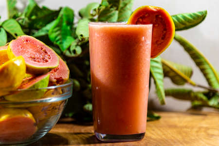 Guava juice and fruits (Psidium guajava). Guava is the fruit of guava. The guava has a tortuous trunk, with a smooth bark, which, when it grows old, comes off in thin brown blades. 版權商用圖片