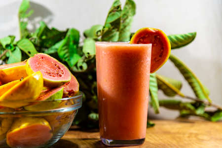Guava juice and fruits (Psidium guajava). Guava is the fruit of guava. The guava has a tortuous trunk, with a smooth bark, which, when it grows old, comes off in thin brown blades.