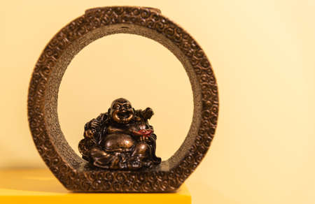 Image of a smiling buddha. The fat and smiling Buddha figure symbolizes serenity and wisdom to achieve spiritual peace.
