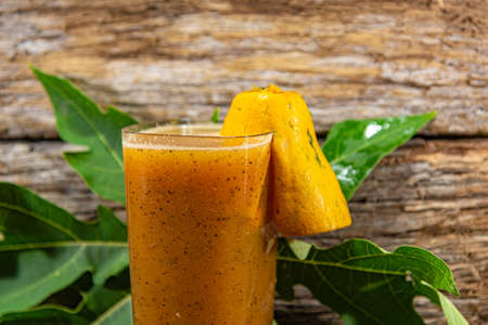 Papaya. Tropical fruits. On a wooden background. Front view. Glass of juice. Refreshment. Detox diet. Morning feeding. Intestinal regulation. Body's health. Fitness food.