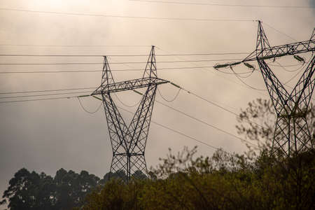 Electricity transmission towers. Dawn in southern Brazil. Energy infrastructure. Electricity conduction lines. Rural landscape at dawn.
