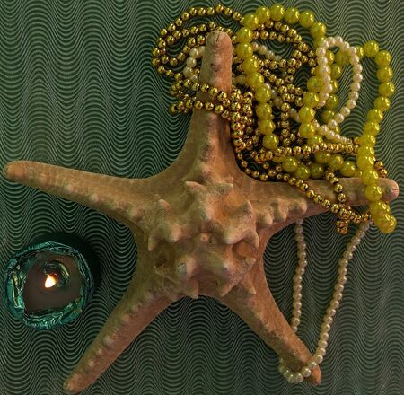 starfish on a green background with a beads and a candle Reklamní fotografie
